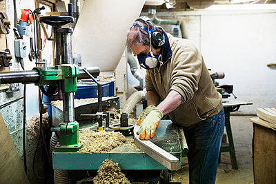 Man standing in a carpentry workshop, wearing a respirator and hearing protector, working on a piece of wood. - p1100m1157567 by Mint Images