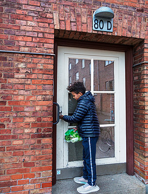 Boy opening door - p312m2139232 by Pernille Tofte