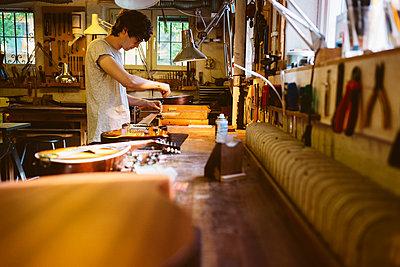 Craftsman working in guitar making workshop - p352m2041523 by Folio Images