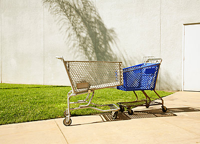 Two shopping trollies touching each other - p429m1494660 by Seb Oliver