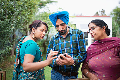 Family texting on cell phone outdoors - p555m1303966 by Donald Iain Smith