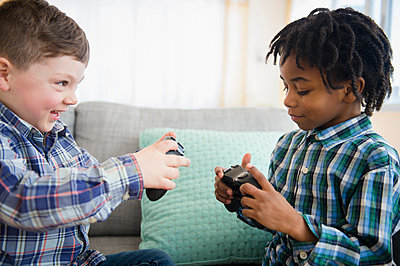Boys playing video games on sofa - p555m1410976 by JGI/Jamie Grill