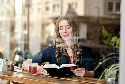 Woman in cafe reading book - p890m1440028 by Mielek