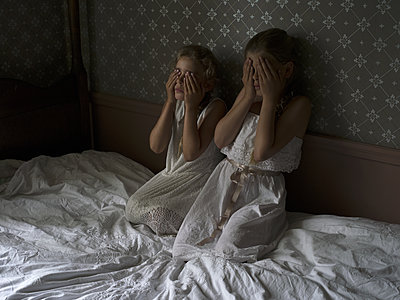 Two girls on bed are scared of something - p945m1155027 by aurelia frey