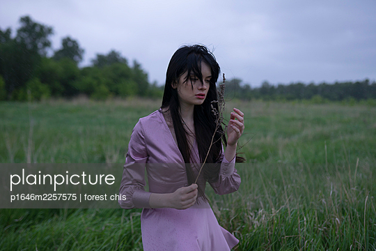 Woman in purple dress holding blade of grass - p1646m2257575 by Slava Chistyakov