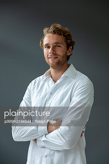 Portrait of young smiling businessman, wearing white shirt, looking at camera - p300m2156544 by Robijn Page
