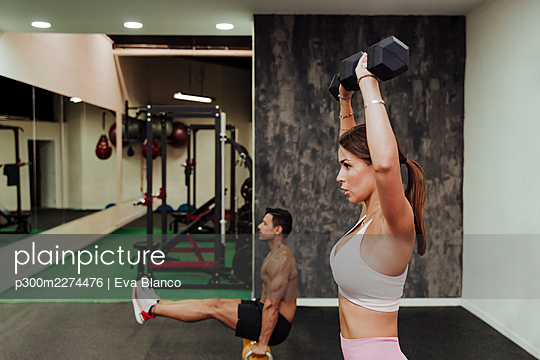 Male and female athlete exercising with equipment at gym - p300m2274476 by Eva Blanco