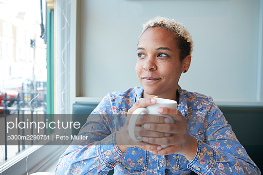 Mid adult woman looking through window while holding coffee cup sitting at cafe - p300m2290781 by Pete Muller