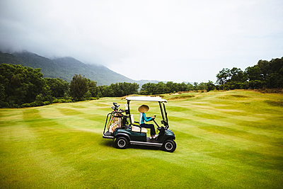Woman wearing traditional straw hat driving golf cart on the green of a golf course under a cloudy sky. - p1100m2164732 by Mint Images