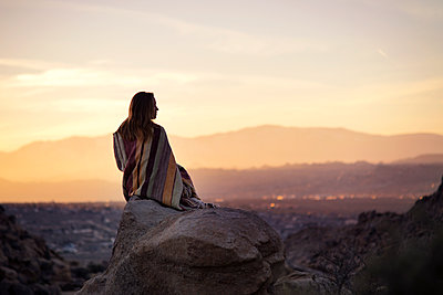 Rear view of woman wrapped in blanket sitting on rock against sky during sunset - p1166m1406821 by Cavan Images