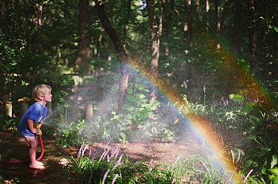 Junge spielt mit Gartenschlauch - p1169m993960 von Tytia Habing