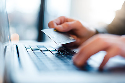 Man using laptop and holding credit card, close-up - p300m1550212 by Daniel Ingold