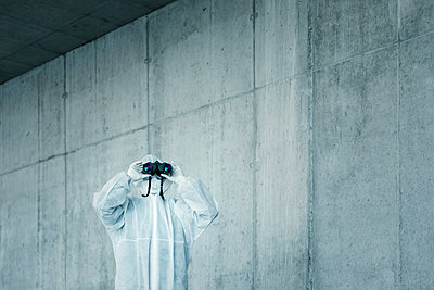 Man wearing protective clothing looking through binoculars - p300m2170902 by Valentin Weinhäupl