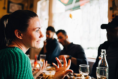 Smiling young woman gesturing while sitting in restaurant during brunch party - p426m2046319 by Maskot