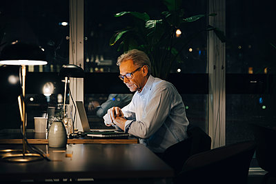 Dedicated senior male professional working late at creative workplace - p426m2194732 by Maskot