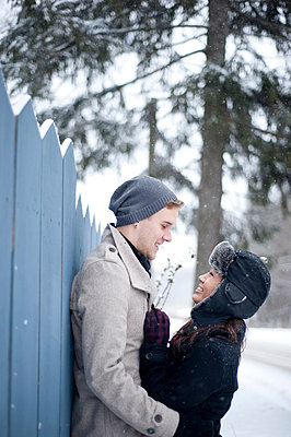 Young couple hugging against fence in snow - p429m2050894 by Sara Monika