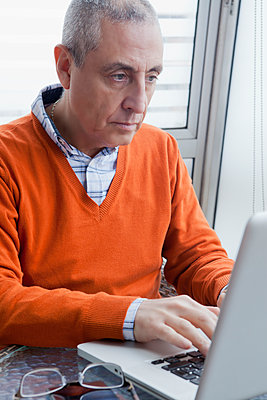 Hispanic man using laptop - p555m1301692 by REB Images