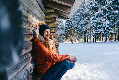 Young woman in winter clothing at log cabin - p586m2005080 by Kniel Synnatzschke