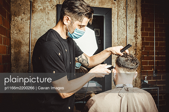 beautician and hairdresser working with mask for the covid19 virus - p1166m2200266 by Cavan Images
