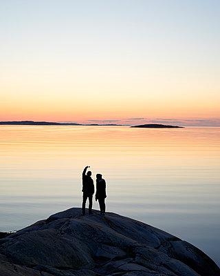 Paar macht Selfie an Schärenküste im Abendlicht  - p1124m1133256 von Willing-Holtz
