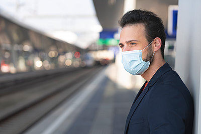 Male entrepreneur looking away while wearing protective mask on railroad station platform - p300m2226243 by Epiximages