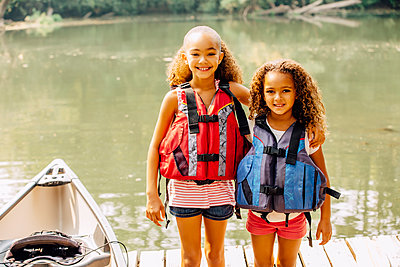 Mixed race sisters wearing life jackets at lake - p555m1306252 by Inti St Clair