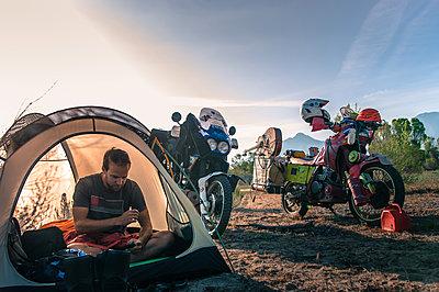Biker using mobile phone inside tent, Fresno, California, USA - p924m2022805 by Alex Eggermont