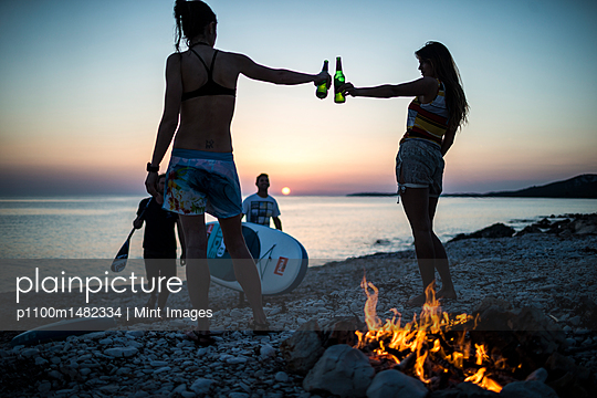 A group of young people gathered on a beach by a campfire.