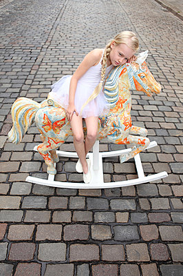 Girl sitting on her rocking horse - p045m853387 by Jasmin Sander