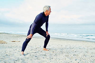 Senior man wearing wetsuit standing on a sandy beach. - p1100m1177568 by Mint Images