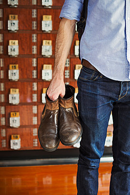 A man holding boots in his hand, shoe lockers in rows behind him.  - p1100m1531130 by Mint Images