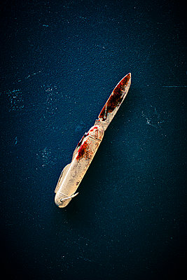 Rusty pocket knife or penknife covered in blood and lying on a scratched black surface - p1302m2092518 by Richard Nixon