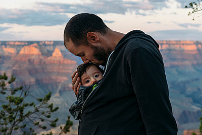 USA, Arizona, Grand Canyon National Park, father kissing baby girl at sunset - p300m1587059 von Gemma Ferrando