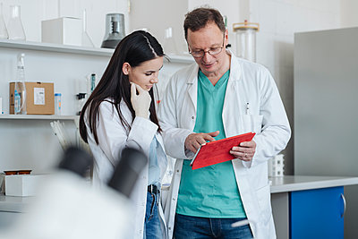 Scientists in white coats using tablet in lab - p300m2250267 by Hernandez and Sorokina