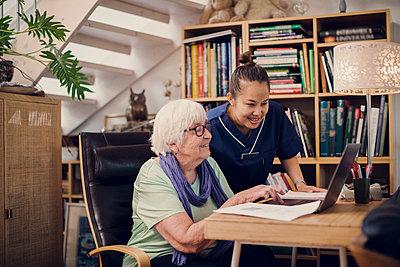 Senior woman and caregiver using laptop - p312m2249450 by Plattform