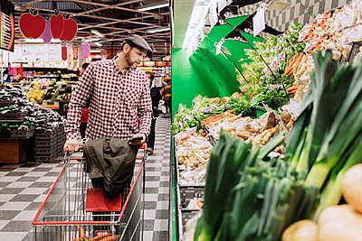 Man holding smart phone while choosing vegetables in supermarket - p426m1148163 by Maskot