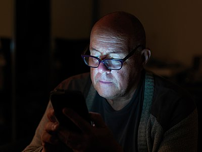 Mature man using smartphone at night, face illuminated - p429m1052779 by Elke Meitzel