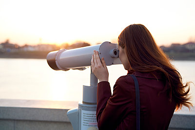 Caucasian woman using binoculars at waterfront - p555m1482007 by Dmitry Ageev