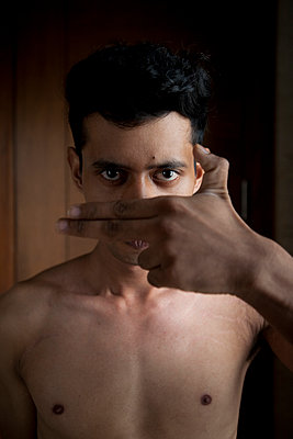 Young male Indian makes finger gun gesture - p817m1589110 by Daniel K Schweitzer