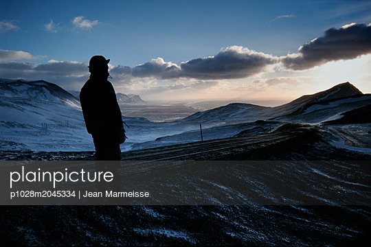 Man looking far away, Route 54, Snaefellsnes peninsula with sea in distance, Iceland - p1028m2045334 by Jean Marmeisse