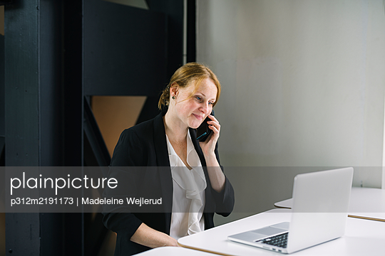 Woman in office talking via cell phone - p312m2191173 by Madeleine Wejlerud