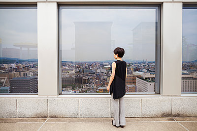 A woman standing looking over a city from a high viewing point.  - p1100m1185886 by Mint Images
