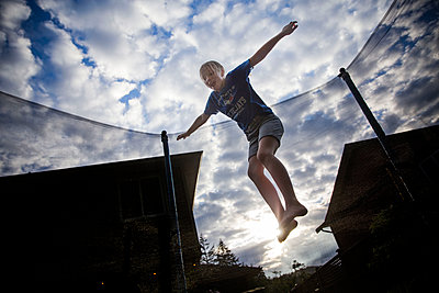 Front view of girl jumping on a trampoline - p1166m2095289 by Cavan Images