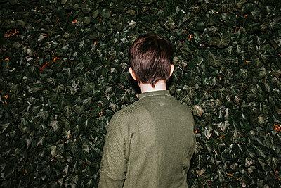 Rückansicht von Teenager vor einer grünen Hecke - p1507m2196557 von Emma Grann