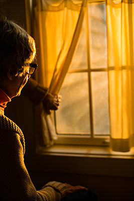 Elderly woman looking out of window - p1614m2211828 by James Godman