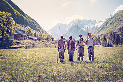 Slovenia, Bovec, four anglers standing on meadow near Soca river - p300m1499283 by Matthias Buchholz