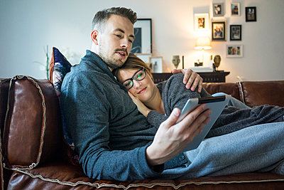 Smiling couple lying on couch at home sharing tablet - p300m1535385 by Robijn Page