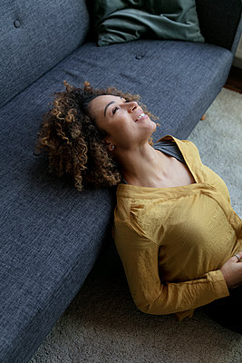 Smiling young woman leaning on couch at home - p300m1536231 by harry + lidy