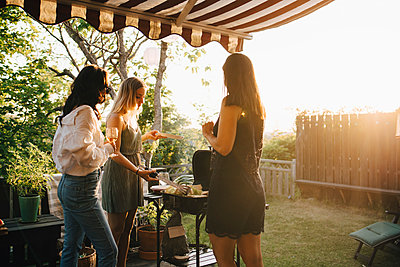 Female friends talking while preparing food on barbecue grill in dinner party - p426m2097334 by Maskot