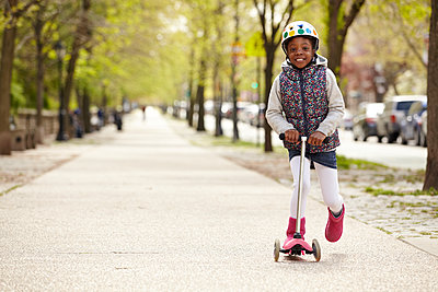 Mixed race girl riding on push scooter on sidewalk - p555m1479789 by Granger Wootz